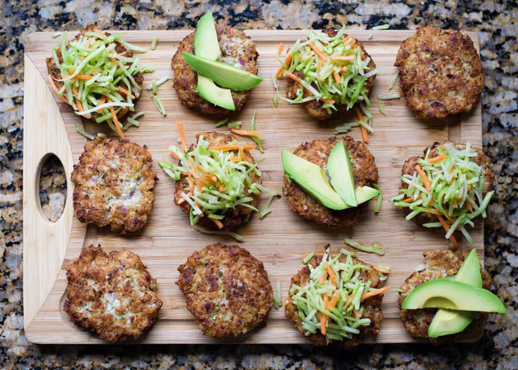 chicken patties topped with avocado and coleslaw on cutting board