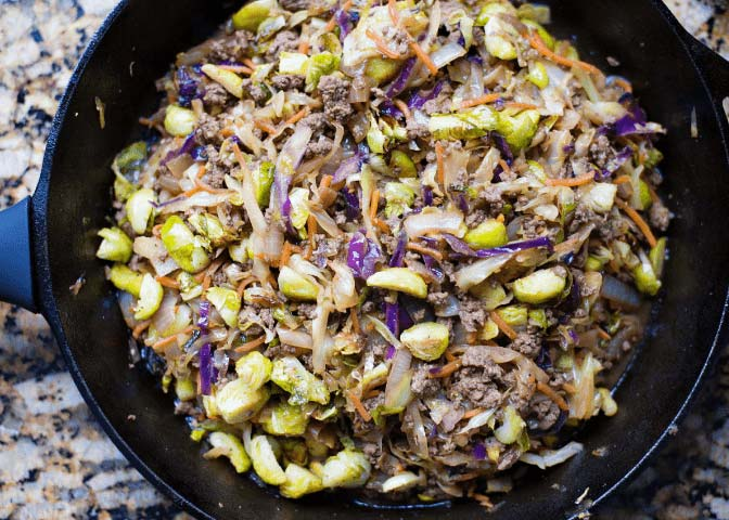 close-up of cabbage stir fry with brussel sprouts in cast iron skillet